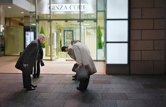 Group of Japanese colleagues bowing; Tokyo, Japan